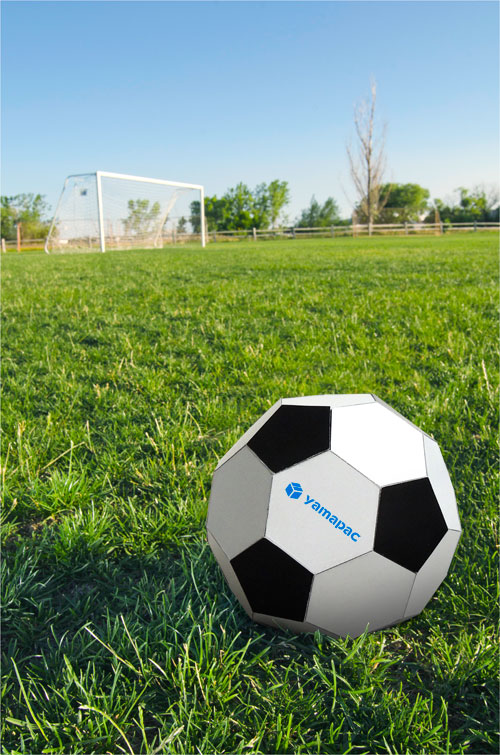 芝生に転がる紙製サッカーボール